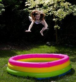 skacząca do kolorowego dmuchanego basenu dziewczynka